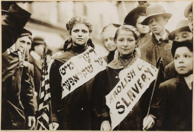 "Two girls wearing banners with slogan ""ABOLISH CH[ILD] SLAVERY!!"" in English and Yiddish (""(ני)דער מיט (קינד)ער שקלאפער(ײ)"", ""Nider mit Kinder Schklawerii""), one carrying American flag; spectators stand nearby. Probably taken during May 1, 1909 labor parade in New York City."