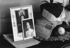 In the Manzanar Relocation Center, in 1943, pictures and mementos sit on top of a radio in the Yonemitsu home.