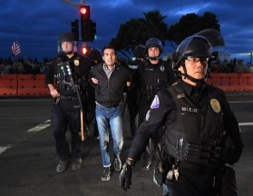 Shmuel Gonzales, activist historian, arrested at Counter-Protest of Alt-Right in Laguna Beach, Calif. Being extracted military-style by five police officers in riot gear after he was himself attacked by fascists.